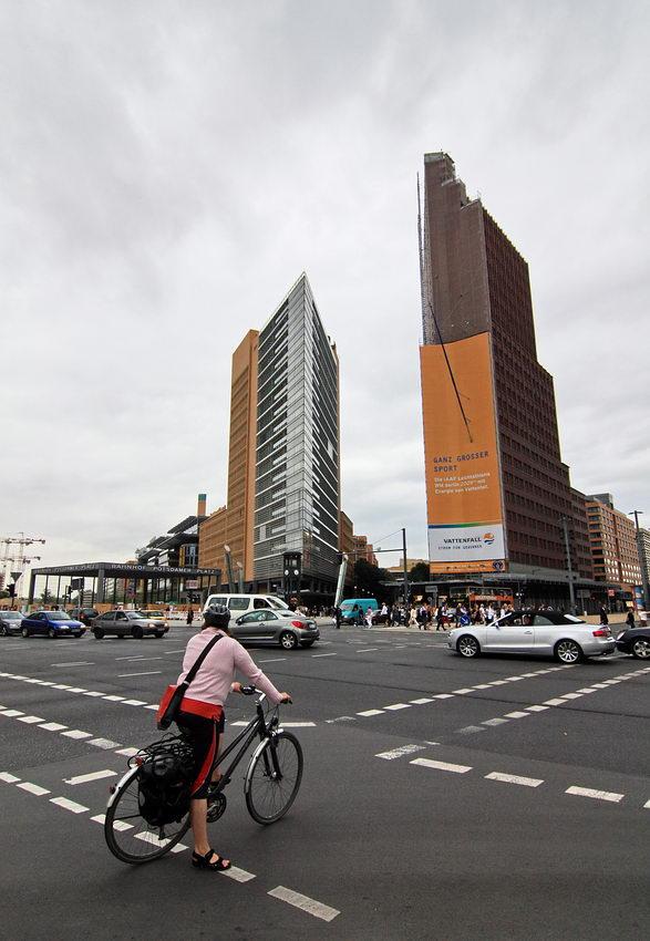 Avenida larga com carros em circulação e uma ciclista à espera de atravessar. Ao fundo edifícios muito altos, perto da Praça Sony.