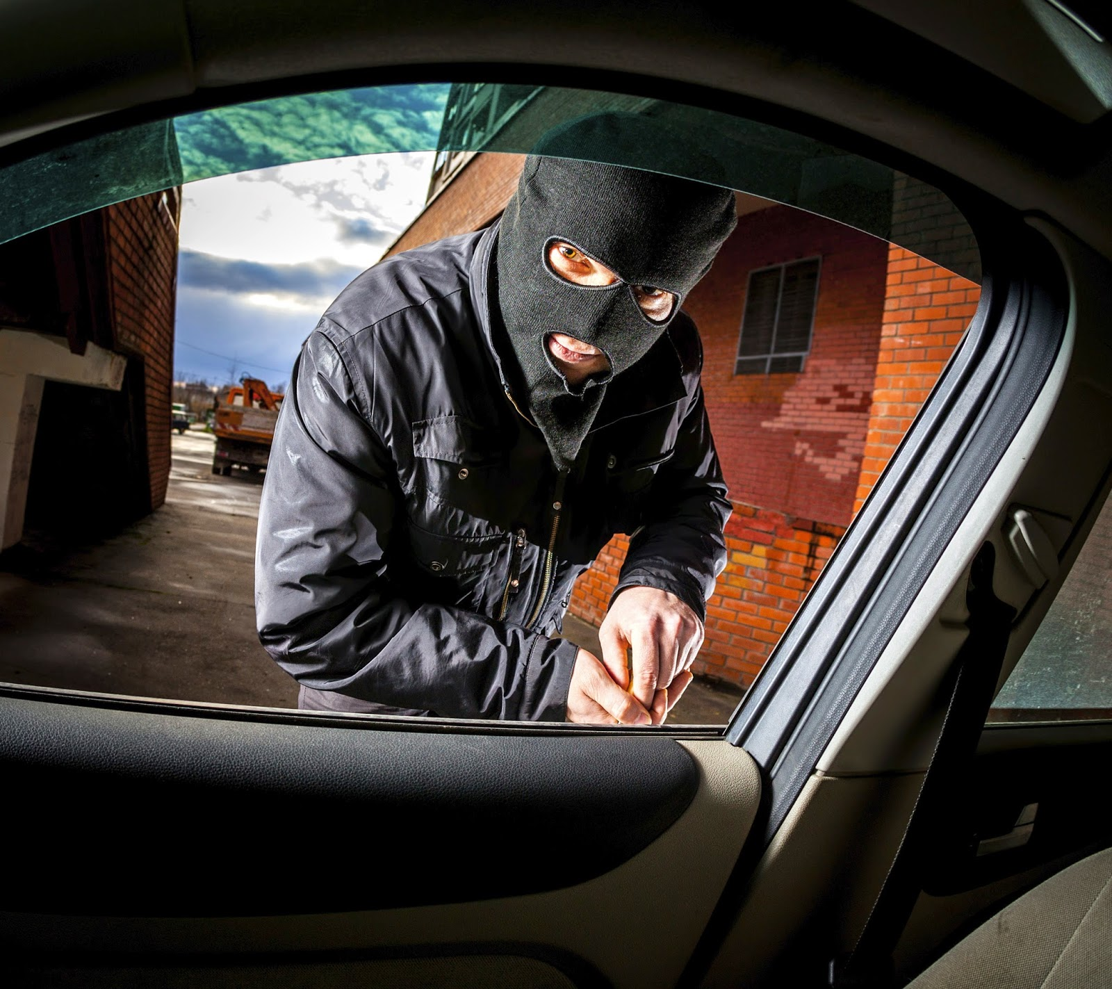 A man in a mask breaking into a car