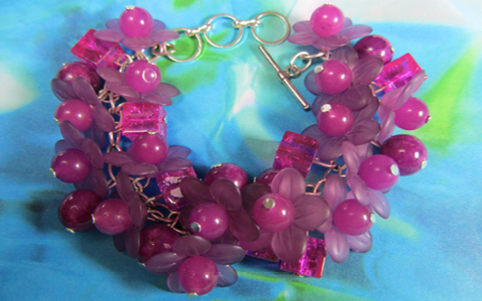 Dramatic bracelet has clusters of square, round and shiny magenta flower beads