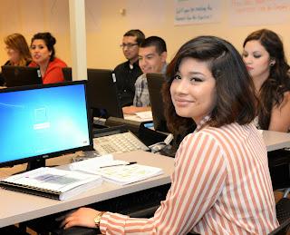 Image af a Rio Salado employee looking at camera, behind her are Rio Salado students.