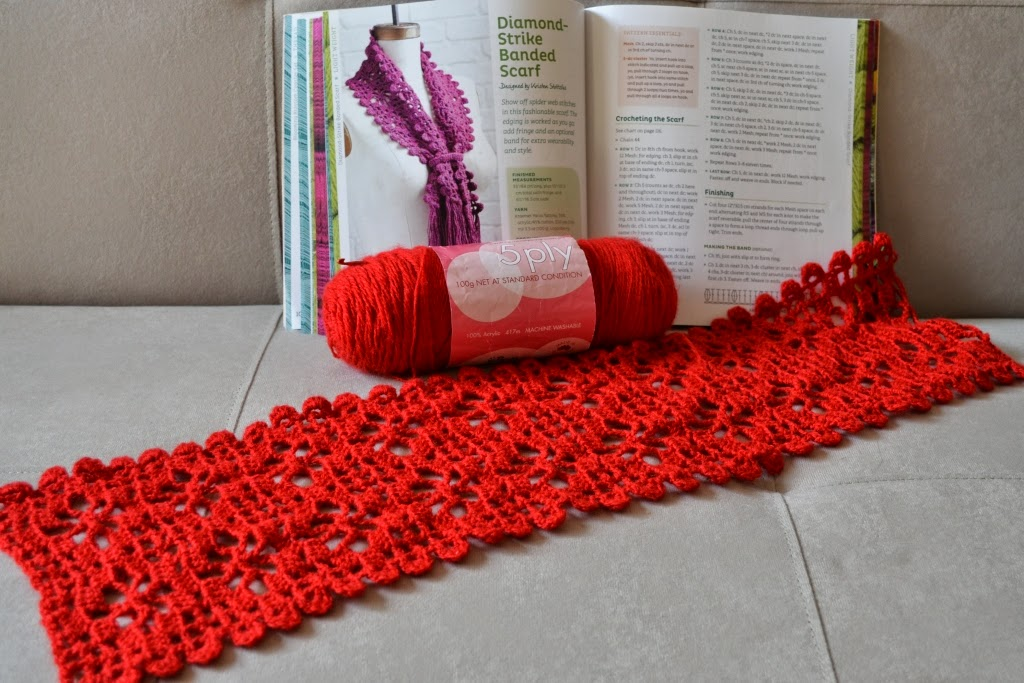 "Diamond-Strike Banded Scarf in progress with yarn (Carnival 5 ply acrylic) and book ""Crochet One-Skein Wonders"" opened up to the ""Diamond-Strike Banded Scarf"" pattern page which shows a photograph of the finished scarf in purple."