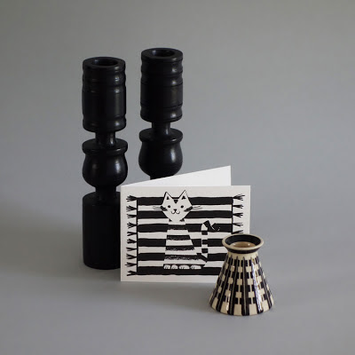 Monochrome cat/kilim card with black wooden candle sticks and an antique ink well