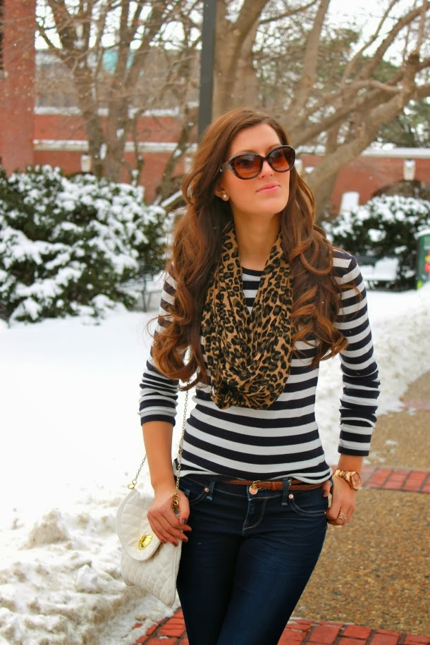 Cheetah skin scarf, black lined sweater, jeans and white hand bag combination for fall
