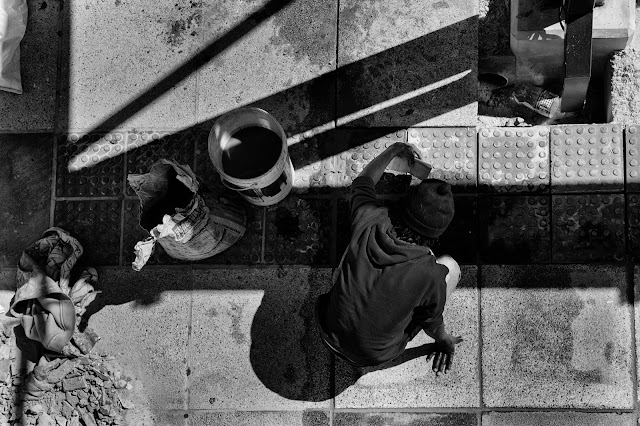 A workman lays bricks in the pavement - shot from above in Cape Town.