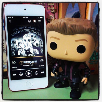 Hawkguy, a bobbleheaded version of Clint Barton, stands beside a red-bordered iPod with We Have Always Lived In the Castle's cover on its screen. The cover features a black and white line drawing of one white person clutching another's shoulders from behind, while more people mill around in the distance.