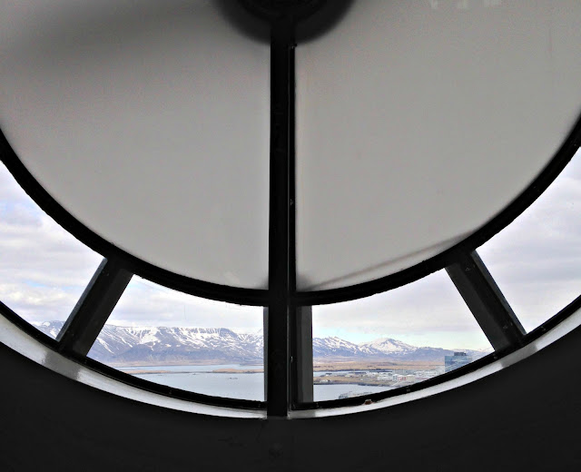 Snowy mountains outside Reykjavik framed by a round window in the spire of the cathedral, Hallgrimskirkja