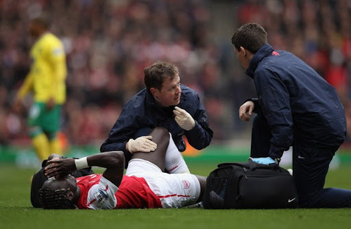 Arsenal player Bacary Sagna receives treatment as he lies injured on the pitch