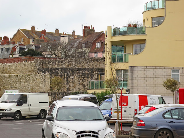 Cars, vans, houses and flats and ruins of old walls.