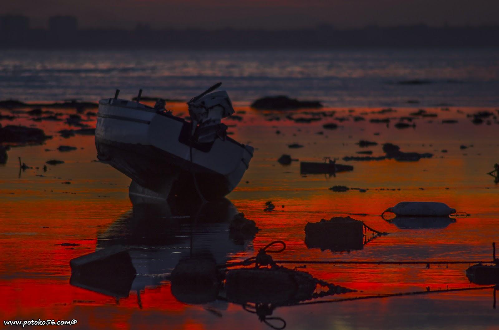 La orilla del chorrillo en la bajamar y una barquilla en el amanecer de Rota