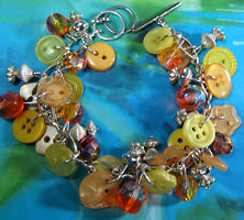 Charm Bracelet has Clusters of Beads and Buttons in Sunshine Yellow with Silver Pewter Charms