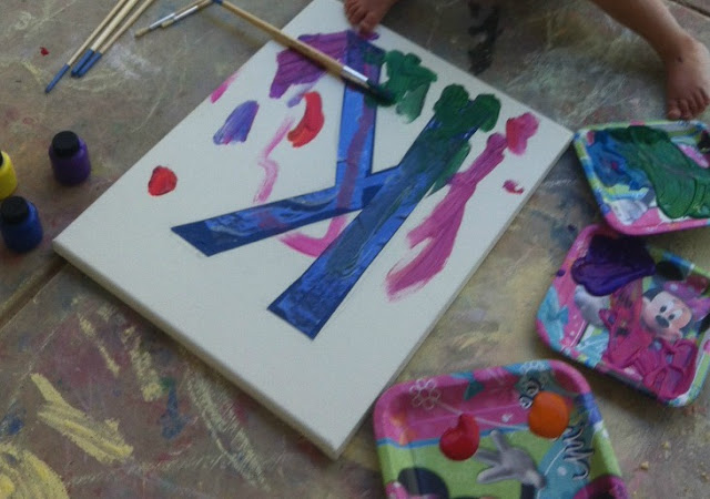 """paints on paper plates and white canvas with the letter """"K"""" taped off partially painted"""