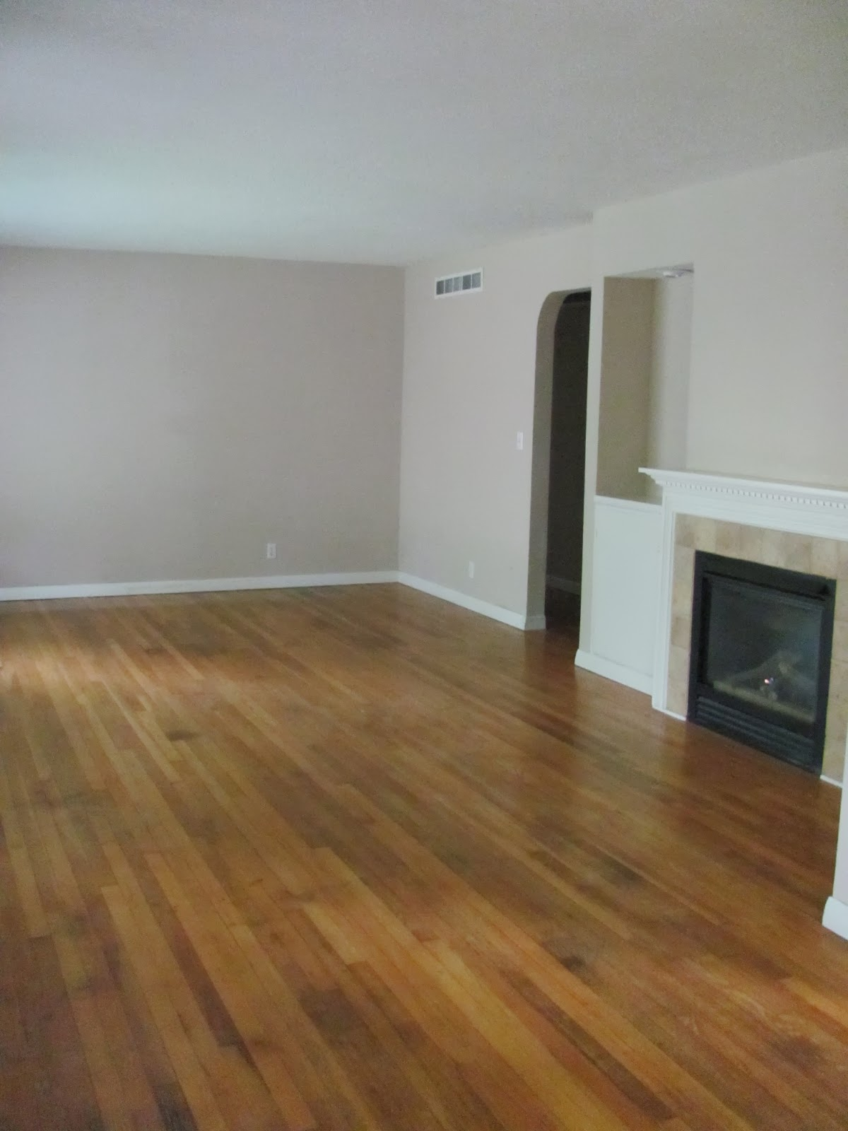 The floors are clean, shiny, and empty in the living room of the old house