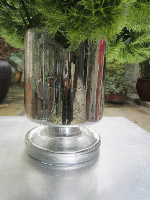 Close up of mercury glass cylinder vase on a metal table on a patio