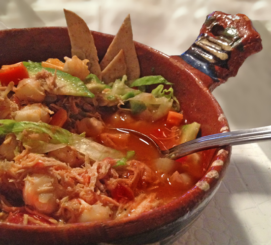 Image close up of chicken posole with shredded chicken in red sauce with sme toppings