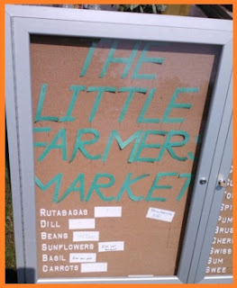 "A photo case discarded from the school is now being used to show produce names and prices underneath big blue letters that say ""The Little Farmer Market"""
