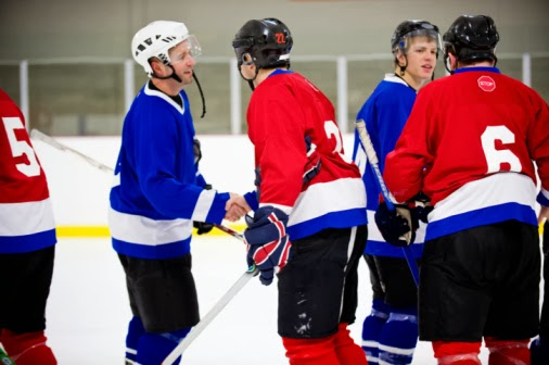 "hockey players in red and blue uniforms shaking hands after a game, saying ""good game"""