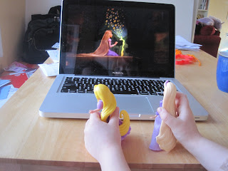 Two Rapunzel dolls being held in front of a laptop showing Rapunzel from Tangled