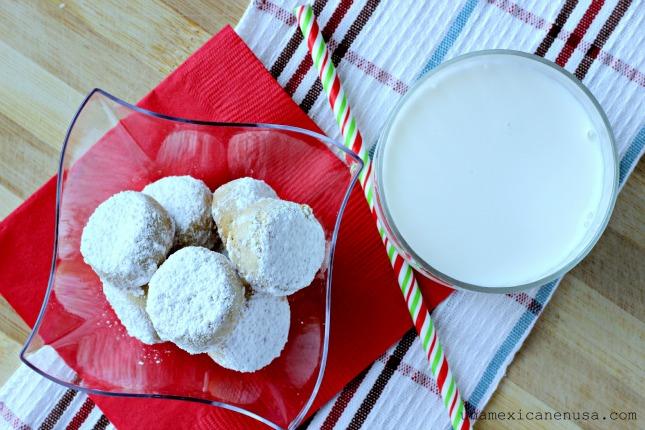 Galletas de nuez espolvoreadas con azúcar glass y servidas con un vaso de leche.