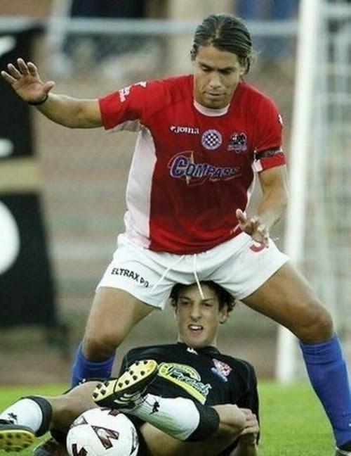smešna slika: fudbaler izmedju nogu protivnika