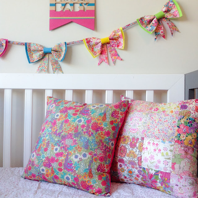 Two Colourful Liberty Cushions On a Cot with Rainbow Bunting Hanging On the Wall