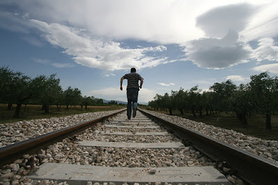 Man running away down a railway track