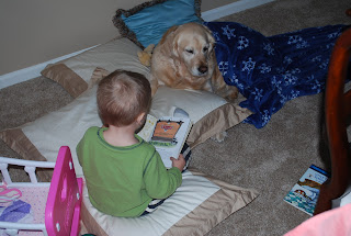 toddler spending time with dog, reading books