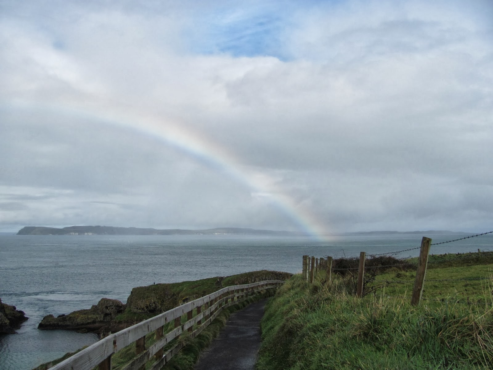 A rainbow stretches to the sea at Carrick-A-Rede Rope Bridge Northern Ireland