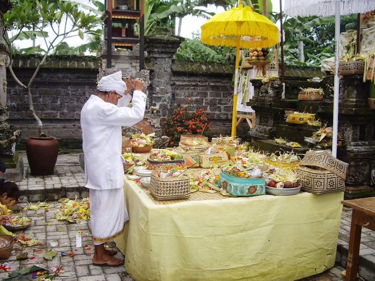 TEMPLE PRIEST PRAYING OVER FOOD OFFERINGS, BALI