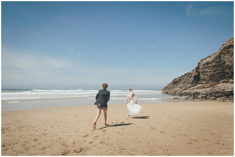 Bride and groom run to the sea