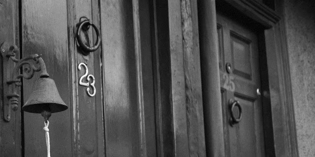 Black and white photograph of two doors, one with number 23 on and the other with 25.