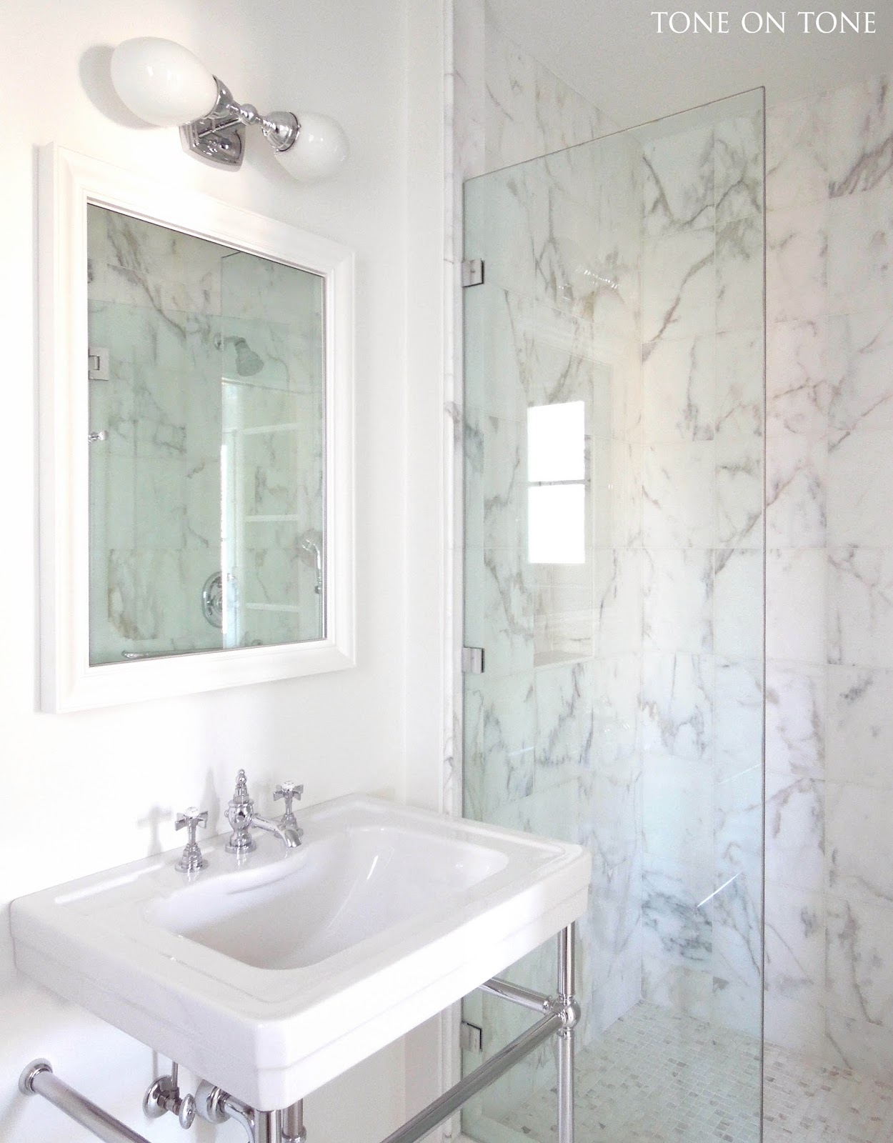 since there is ample storage elsewhere in the bedroom a console sink with open base looks lovely here simple clean and airy ample shower lighting