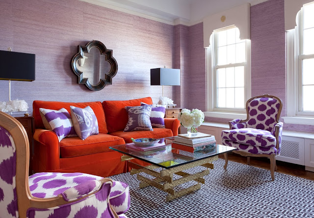 Lavender living room with orange sofa, purple ikat accent pillows and armchairs and a Greek key rug