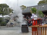 巫女が両手に笹の束を持ち、何回も笹の葉で勢いよく大釜の湯を散らした。
