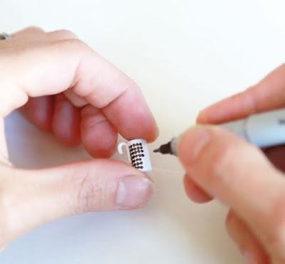 Hands drawing spots on a modern miniature Marimekko Siirtolapuutarha mug.
