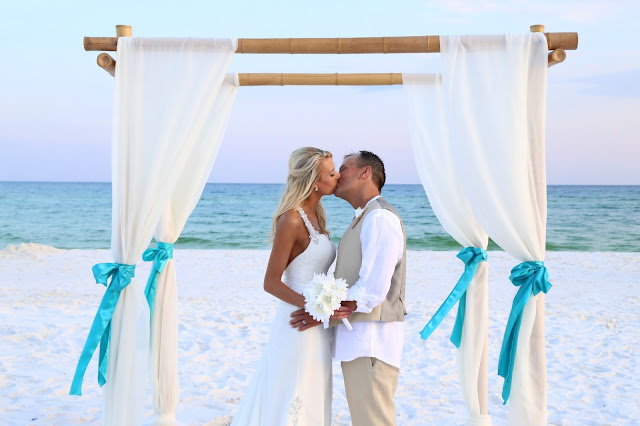 Decorated bamboo wedding arbor for your Destin Beach Wedding, turquoise and ivory fabric and sashes
