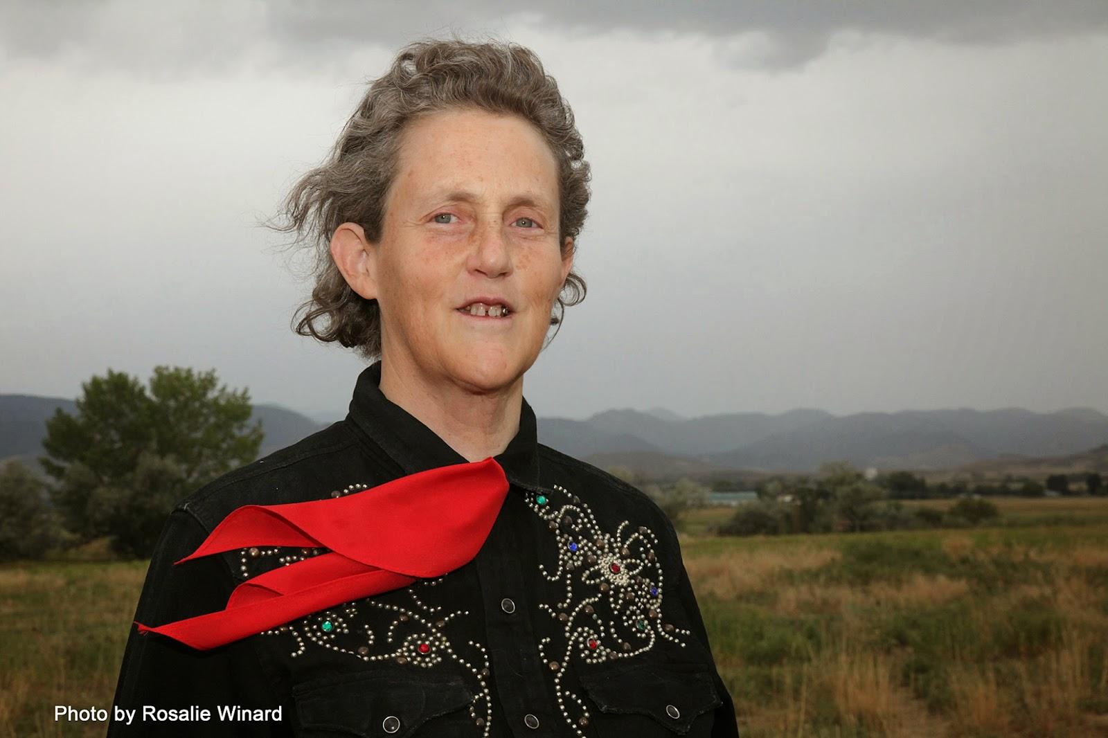 Usmívající se Temple Grandin s černou vyšívanou košilí a červeným šátkem