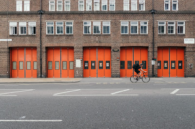 bicyclist passing brick building with five garage doors, four panels each, all bright orange