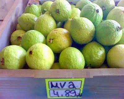 Banca de frutas contendo goiabas, mas com placa anunciando o preço da uva.