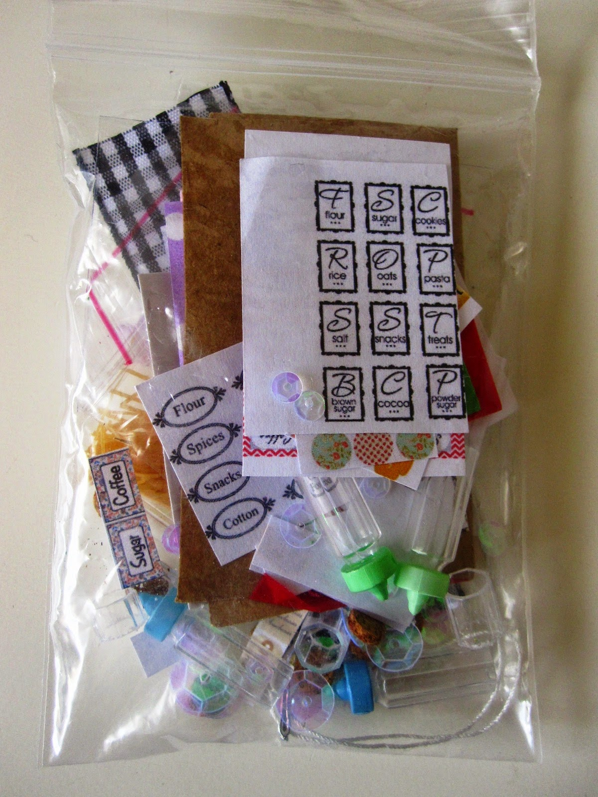 Small ziplock bag filled with tiny dolls' bottles and a selection of printies for making miniature jars.