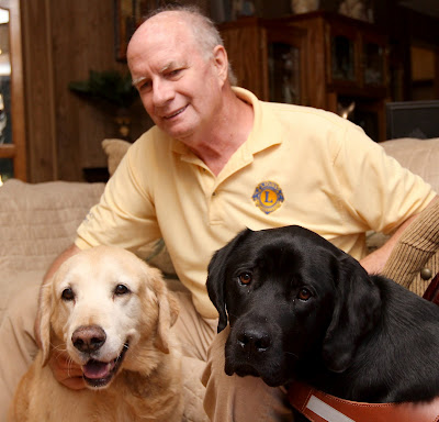 Golden Galleon and black Lab Brinkley by the side of Larry Marcum