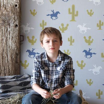 Hibou Home Cactus Cowboy Kids Wallpaper. Beautiful action packed wild west themed wallpaper. A cool grey background, with cowboys on horses with lassos at the ready in muted denim blue with white hues. Dusty green coloured cacti with blue detailing adds a lovely finishing touch. The picture features a boy sitting on a bale of hay with wallpaper as the background.