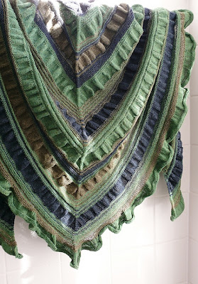 Gathered Triangle is a triangle shaped shawl featuring multicoloured stripes followed by solid stockinette stitch ruffles