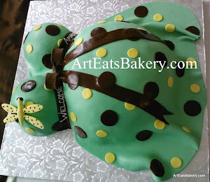 Unique green, yellow, and brown polka dot baby bump shower cake with edible dragonfly and bow