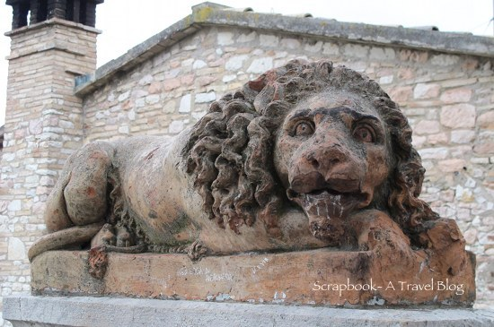 Lion sculpture street-side Assisi Italy