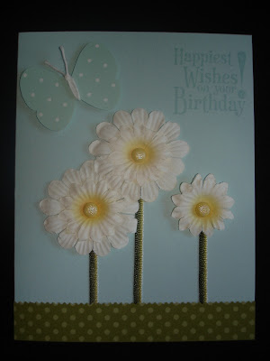 Light blue card with patterned green paper as grass, a punched butterfly and three paper daisies with green ribbon stems.