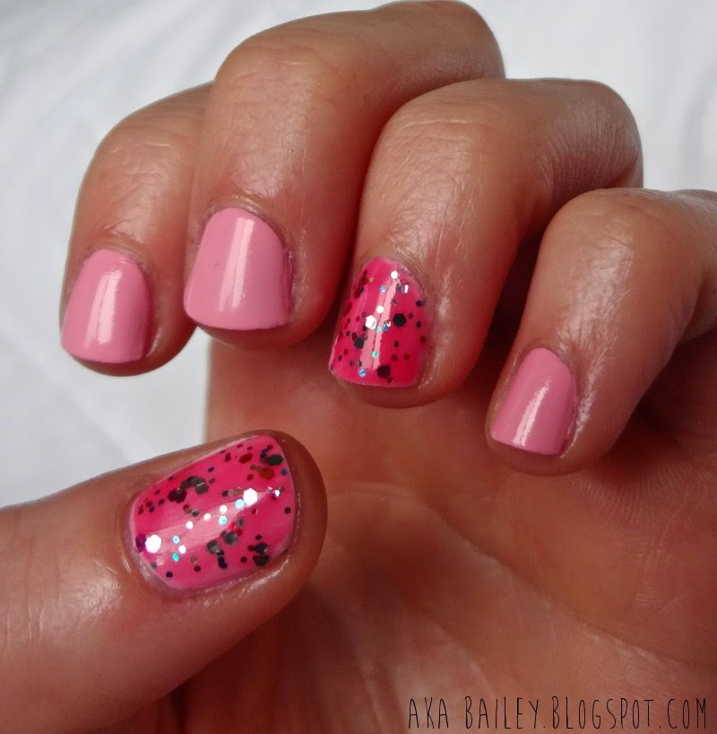 Pastel pink nails with multi-colored glitter accent nails
