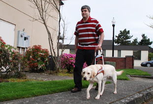 Bob and guide dog Perez walk down the street