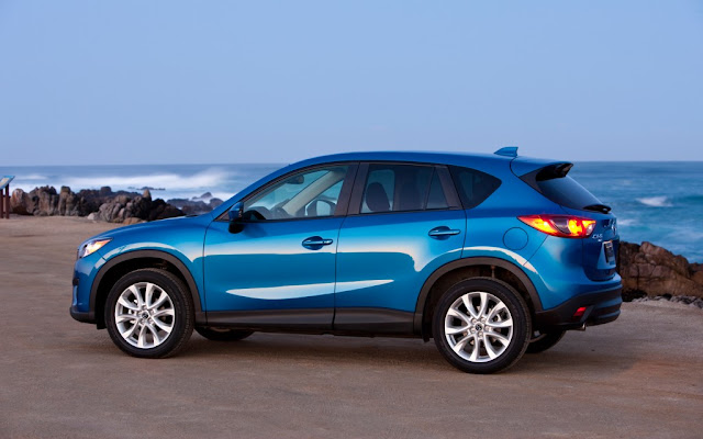 Side view of 2014 Mazda CX-5 Skyactiv in blue at seashore.