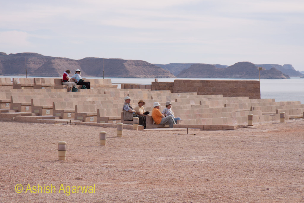 Tourists sitting on rows of stone seats near the Abu Simbel temple in south Egypt