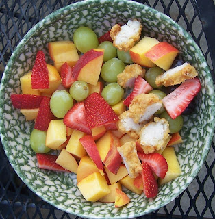 fried chicken tenders cut up in bowl of cut up peaches, cut up strawberries, and white grapes